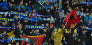 kosovo football fans wave flags in stadium